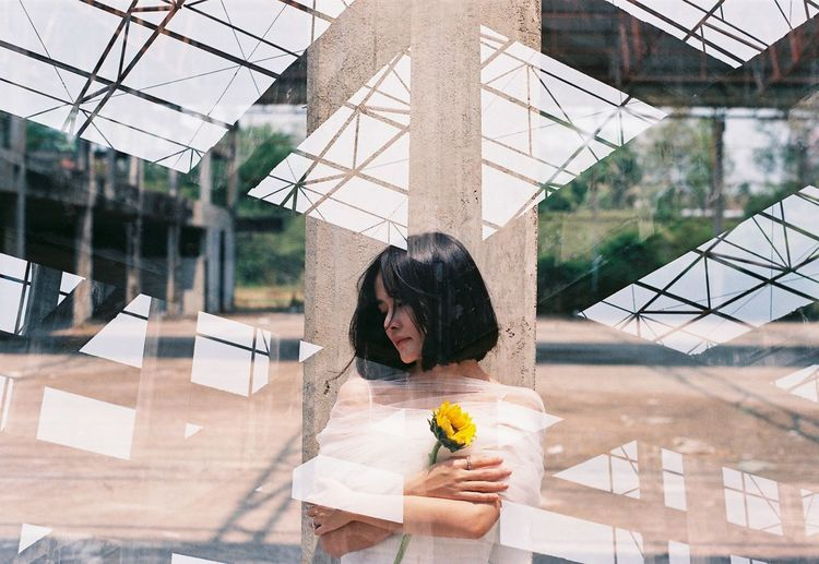 Double exposure of buildings and woman holding sunflower