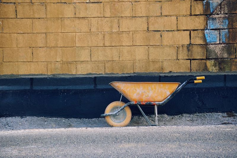 Old yellow wheelbarrow in the street in he construction