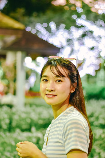 Portrait of a smiling young woman against plants at park