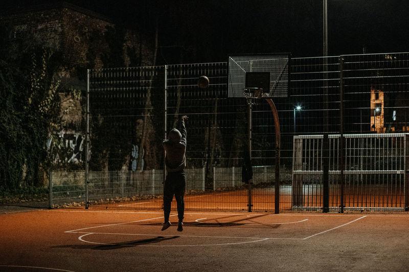 Man playing with basketball hoop at night