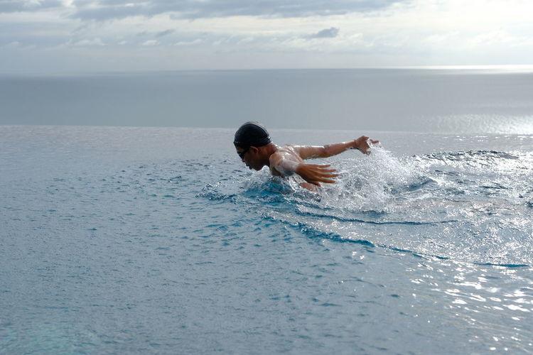 Teenage boy swimming in infinity pool against sea