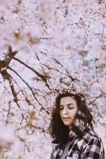 Woman against cherry blossom tree