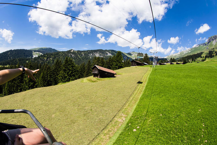 Upwards / cable car view captured in Switzerland - (c) Nidal Sadeq Cable Car Forward Green Alps Beauty In Nature Blue Sky Cloud - Sky Cottage Day Grass Human Body Part Human Hand Lifestyles Meadow Mountain Nature One Person Outdoors People Real People Sky Storage Tree Upward Perspective Upward View An Eye For Travel