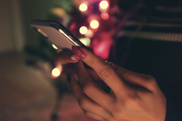 Nail Art Christmas Christmas Lights christmas tree Human Hand Hand Human Body Part One Person Holding Real People Lifestyles Wireless Technology Communication Illuminated Smart Phone Portable Information Device Connection Indoors  Body Part Technology Close-up Focus On Foreground Text Messaging Finger Nail
