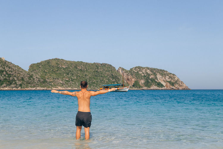 Sea Water Rear View Sky Shirtless Standing Leisure Activity Beauty In Nature Lifestyles Scenics - Nature Beach One Person Clear Sky Land Human Arm Copy Space Three Quarter Length Men Nature Limb Horizon Over Water Arms Raised