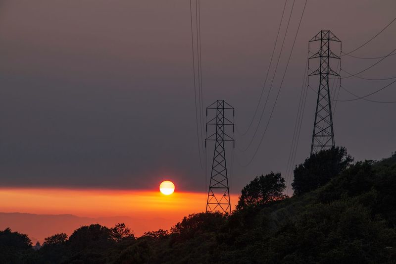 Electricity Pylon Sky Sunset Tree Electricity  Beauty In Nature Technology Electricity Pylon Plant Silhouette Nature No People Scenics - Nature Tranquility Cable Tranquil Scene Connection Orange Color Sun Idyllic