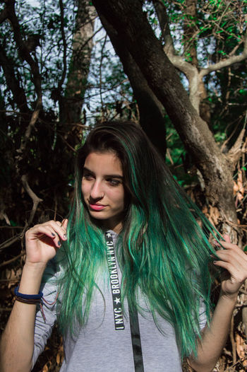 Portrait of beautiful young woman against trees
