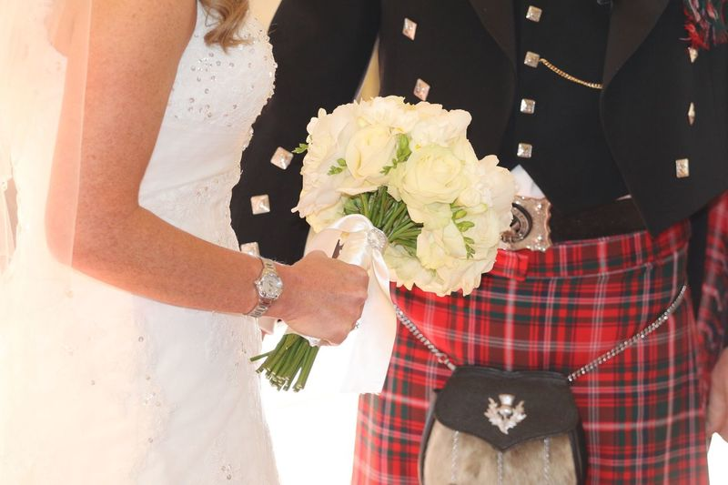 Midsection Of Bride And Bridegroom With Flower Bouquet