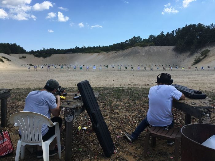 Rear view of fiends practicing with rifle at shooting range