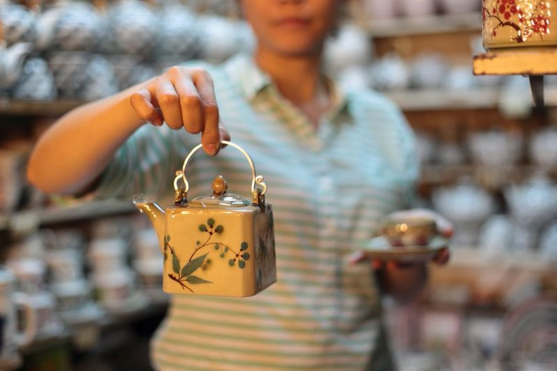 Woman holding teapot in store