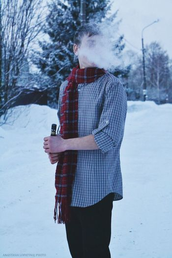 Man Smoking Electronic Cigarette While Standing On Snow Covered Field