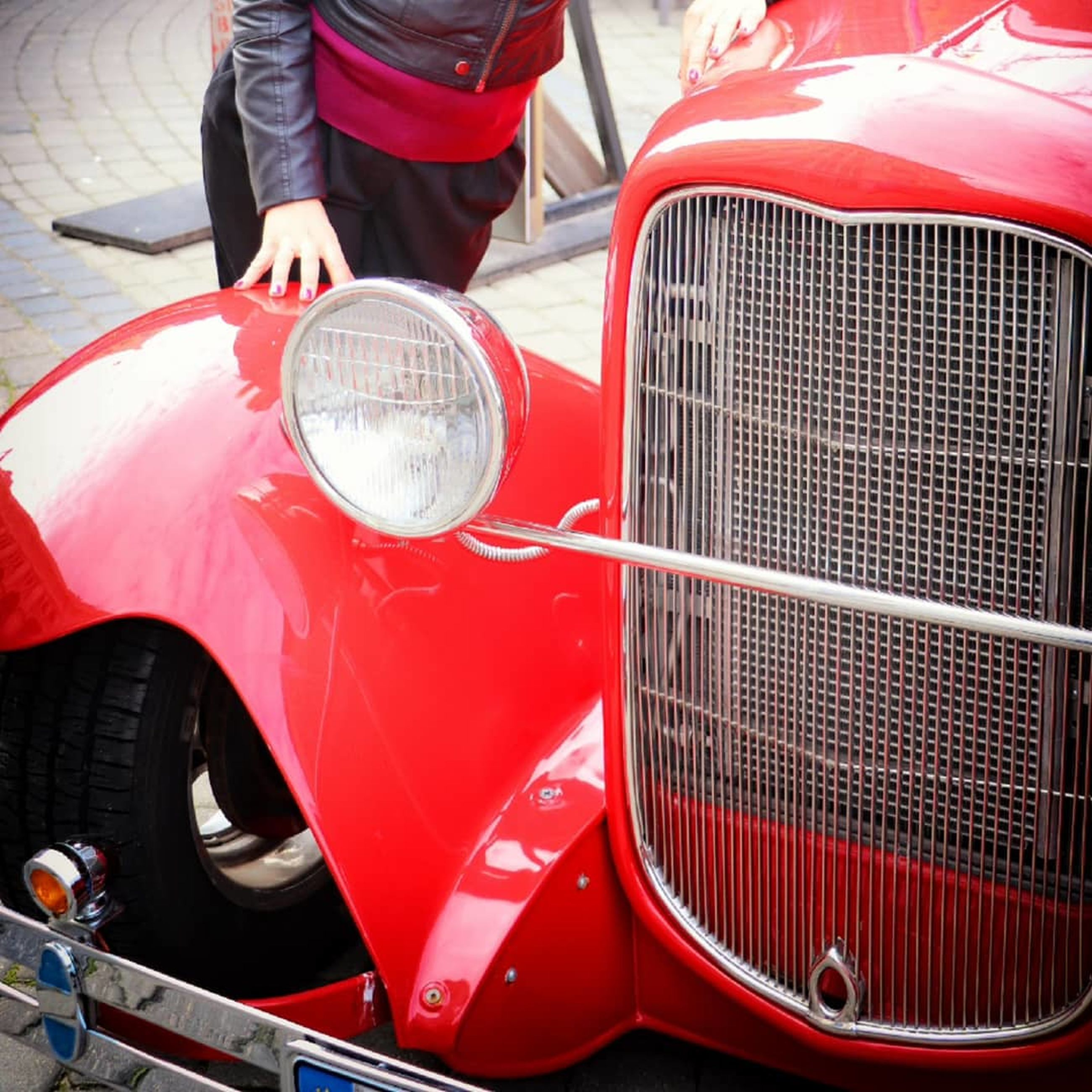 mode of transportation, car, motor vehicle, transportation, land vehicle, red, headlight, day, retro styled, outdoors, focus on foreground, one person, metal, incidental people, vintage car, street, lighting equipment, close-up, luxury, wheel