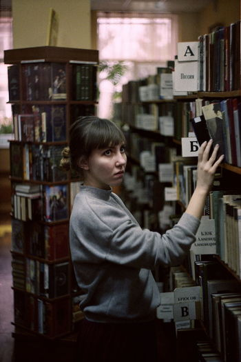 Side view of young woman searching book while standing in library