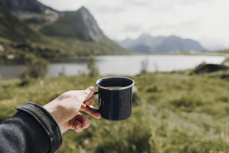 Cropped hand of person holding coffee cup against lake