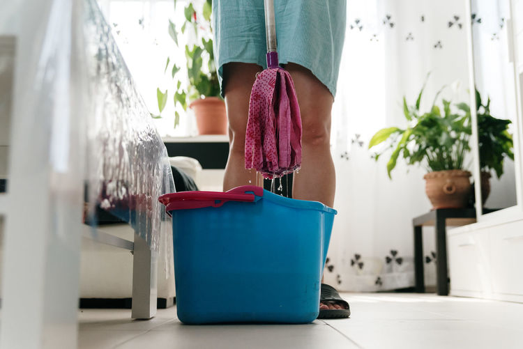 Low section of woman standing on potted plant