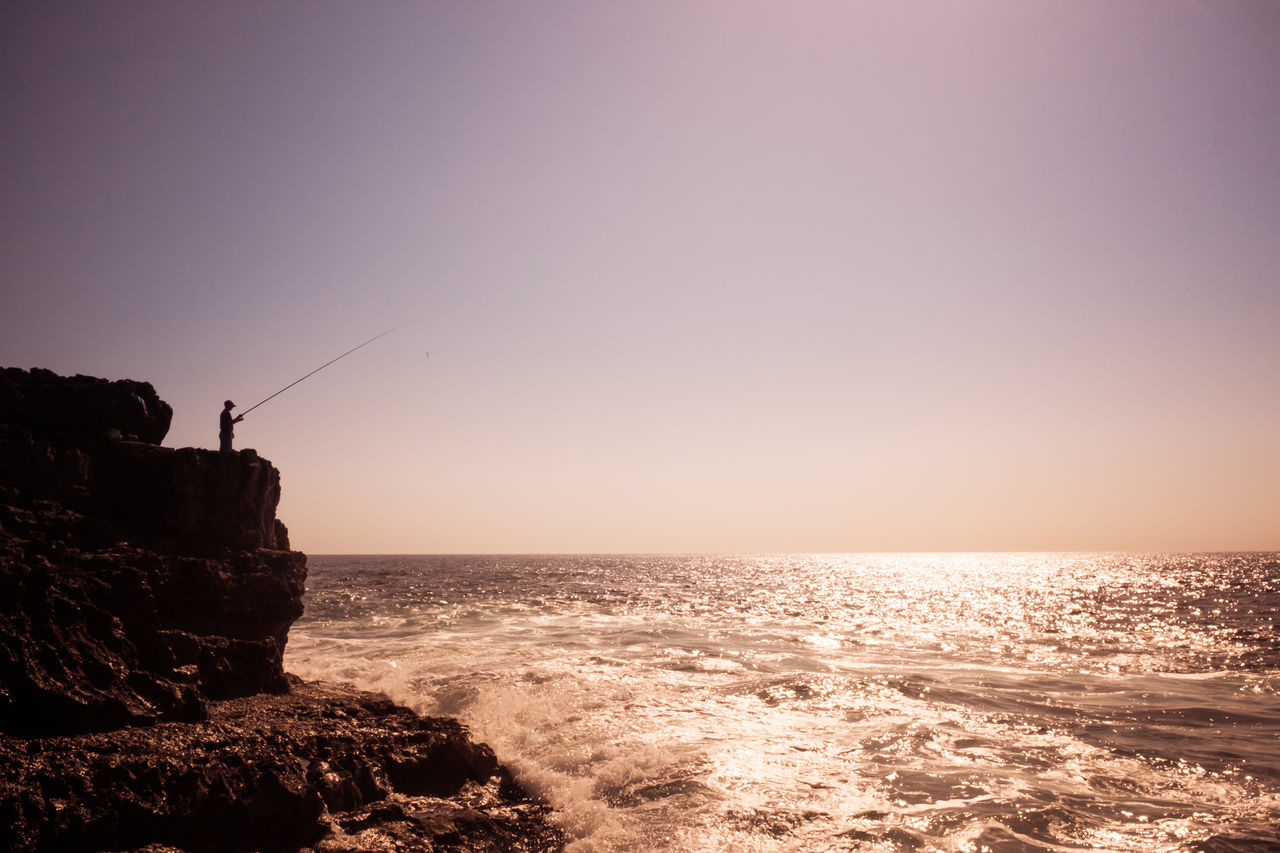Person Fishing While Standing On Rock Formation In Sea Against Clear Sky During Sunset