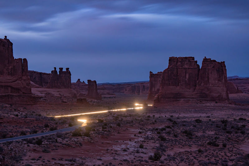 Trail of car lights exiting park through Arches National Park canyon. Arches National Park, Utah Busy Three Gossips Three Gossips, Arches, Astrophotography Milkyway Milkyway Night Beauty In Nature Car Light Cloud - Sky Day Exiting Illuminated Light Trail In The Road Light Trail Photography Light Trails Traffic Cars Busy Nature No People Outdoors Scenics Sky