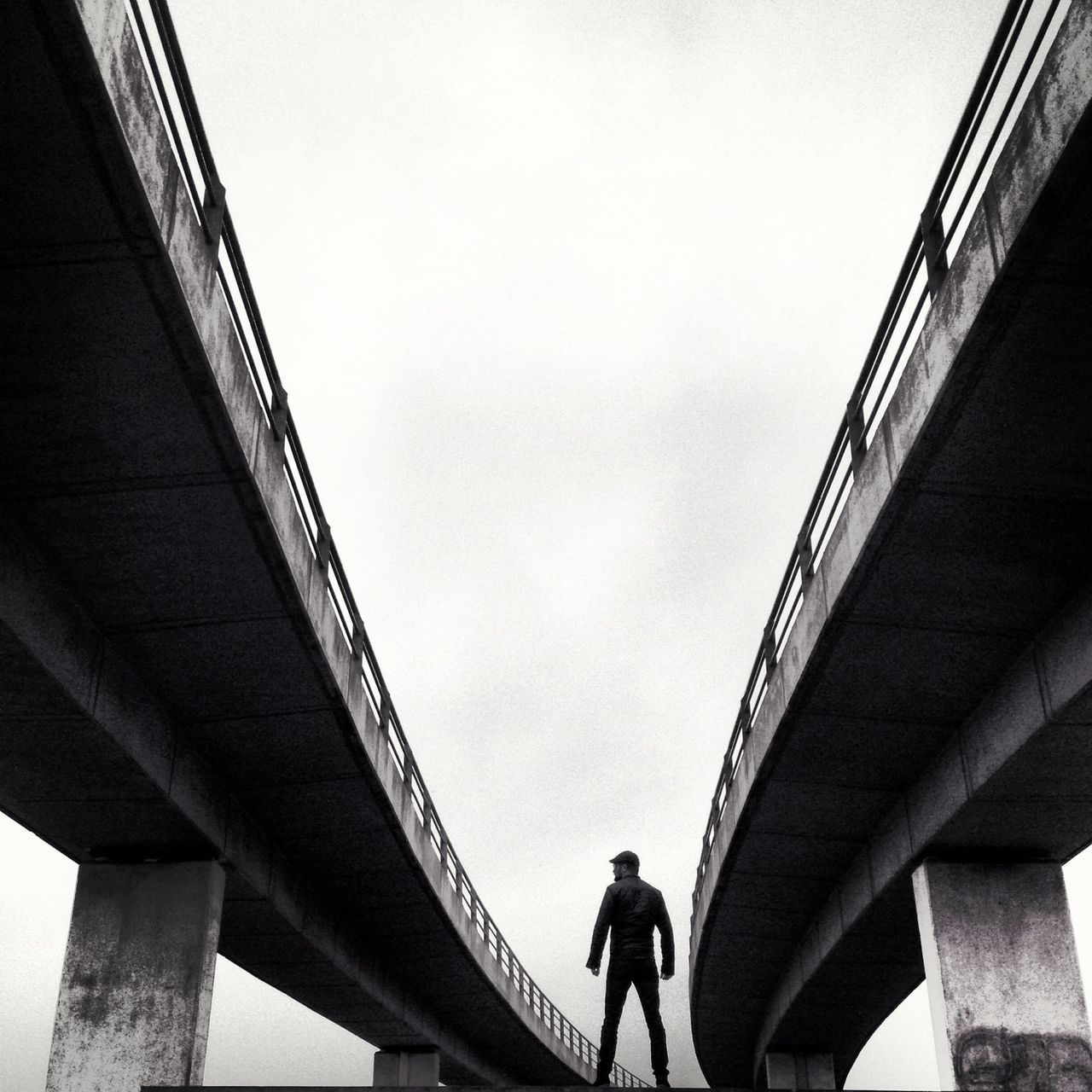 bridge - man made structure, architecture, connection, low angle view, built structure, real people, below, lifestyles, one person, day, transportation, leisure activity, women, standing, outdoors, full length, sky, people