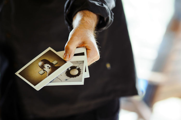 Midsection Of Man Holding Instant Print Transfers