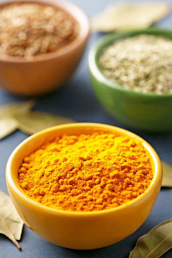 High angle close-up of curry powder with cumin and oregano in bowls on table