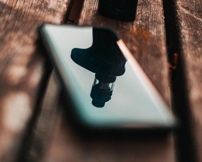 High angle view of mobile phone on wood