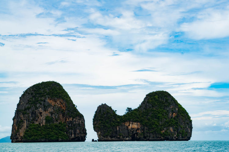 Scenic view of rock island in calm sea against cloudy sky