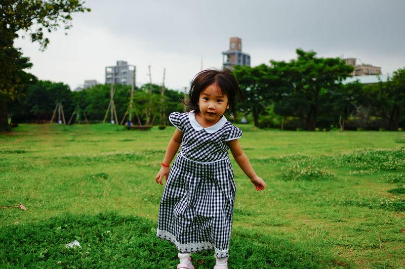 Portrait of girl standing on grassy field