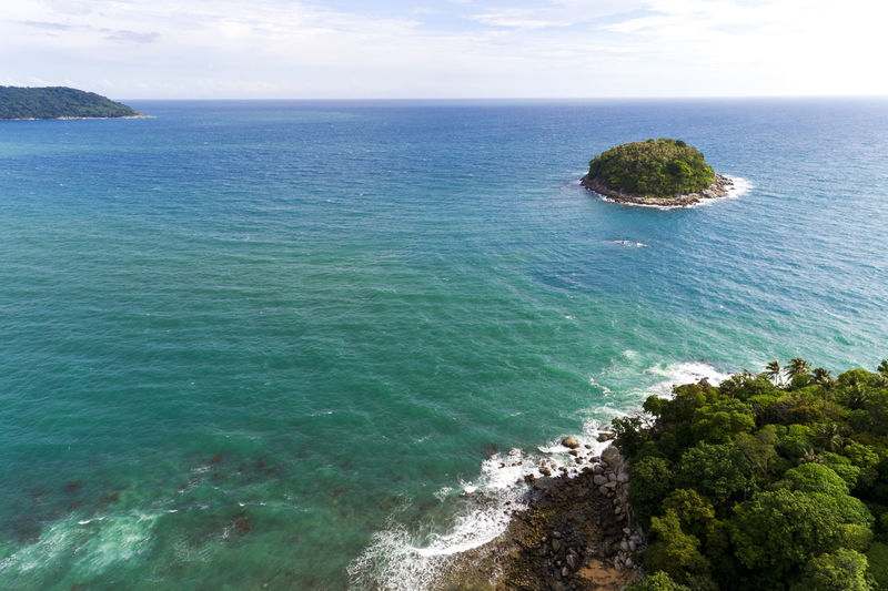 Drone aerial view shot of Tropical sea with beautiful small island in Phuket Thailand. View Drone  Aerial Shot Phuket Beautiful Sea Thailand Island Nature Landscape Tropical Summer Beach Coast Travel Water Scenery Blue Background Sky Green Vacation Ocean Paradise Turquoise Holiday Coastline Tourism Seascape Top Beauty Tree Day Wave Stone ASIA Scenic Rock Boat Shore Bay Clear Outdoor Sunny Mountain Sand Small High Season