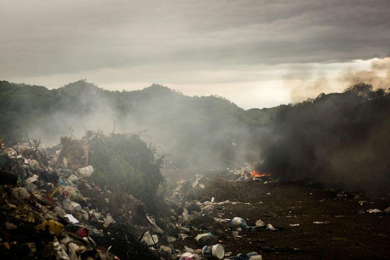 Burning garbage emitting smoke at junkyard