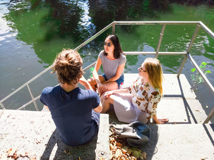 High Angle View Of Friends Sitting On Steps By Lake