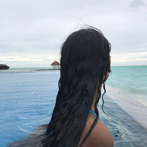 Rear view of woman on in infinity pool against sky