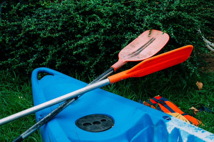 High Angle View Of Kayak And Oars On Field