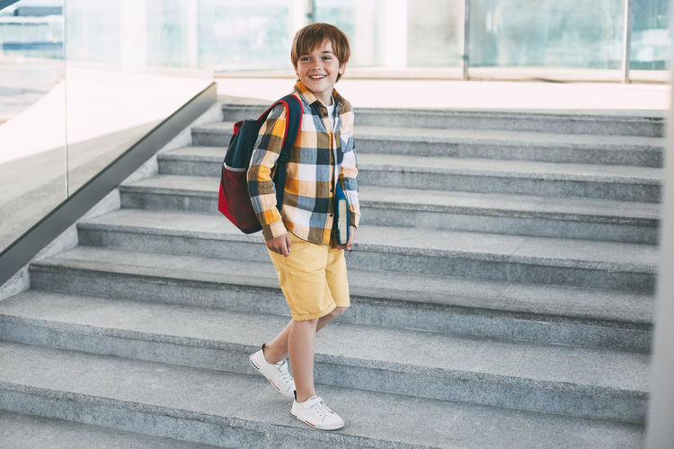 Boy looking away while standing on staircase