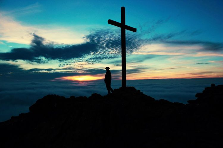 Silhouette man standing on rock by cross against sky during sunset