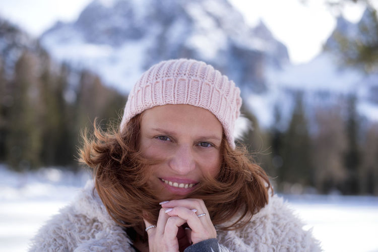 Close-up portrait of mature woman wearing warm clothing and knit hat during winter