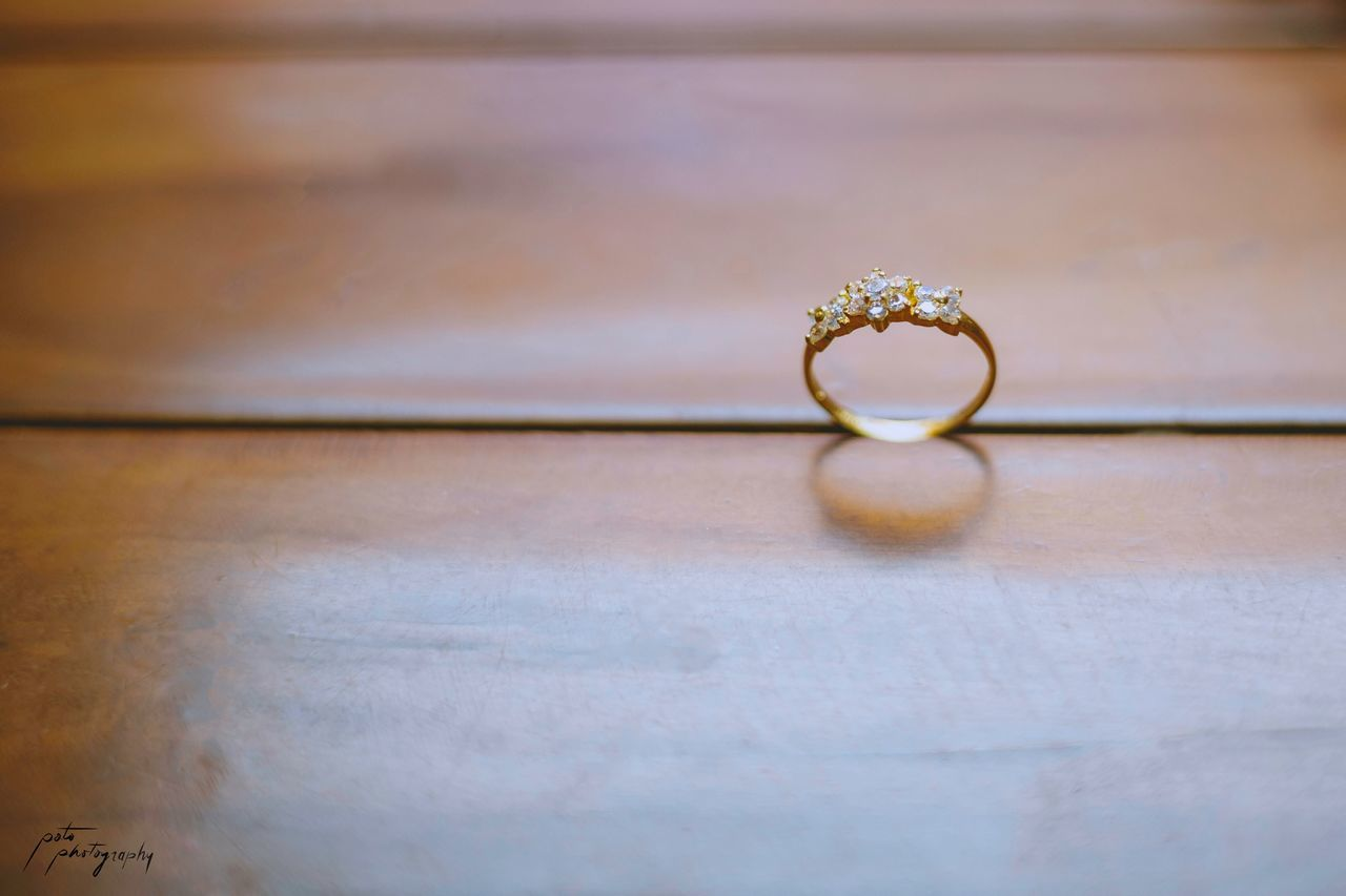 jewelry, ring, close-up, indoors, love, table, still life, wealth, no people, diamond - gemstone, luxury, selective focus, positive emotion, emotion, gold colored, single object, personal accessory, engagement ring, shiny, wedding ring, floral pattern, precious gem