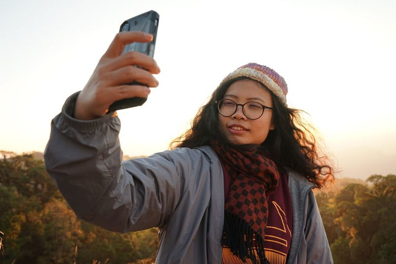 Sunlight Fall Winter EyeEm Selects Wireless Technology Selfie Technology Camera Photography Themes Young Adult Smart Phone Portable Information Device Front View Photographing One Person Portrait Hairstyle Mobile Phone Nature
