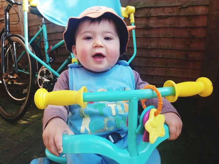 Portrait Of Cute Baby Boy Sitting In Tricycle