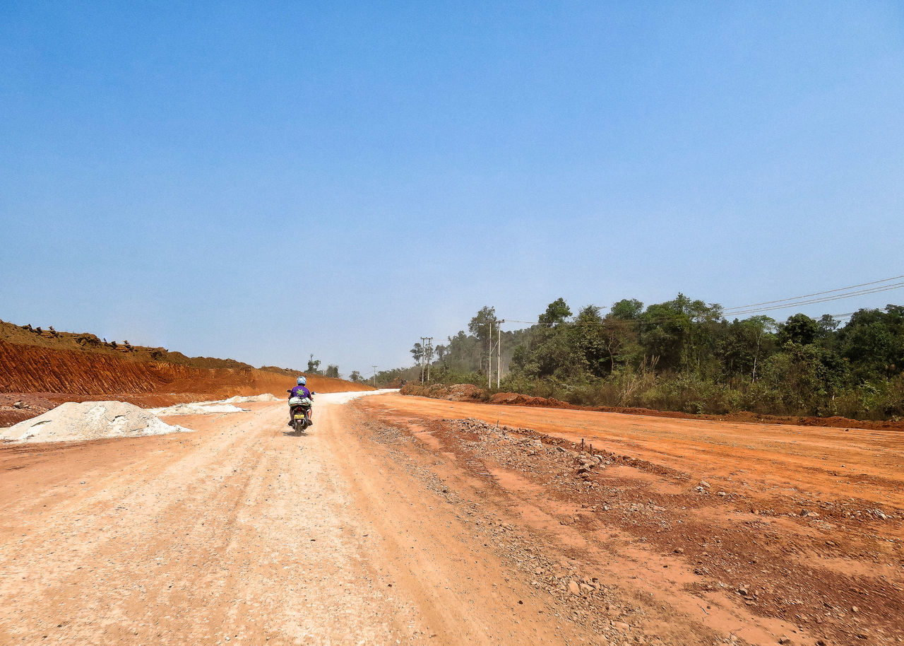 Rear View Of Man Riding Motorcycle On Dirt Road Against Clear Sky