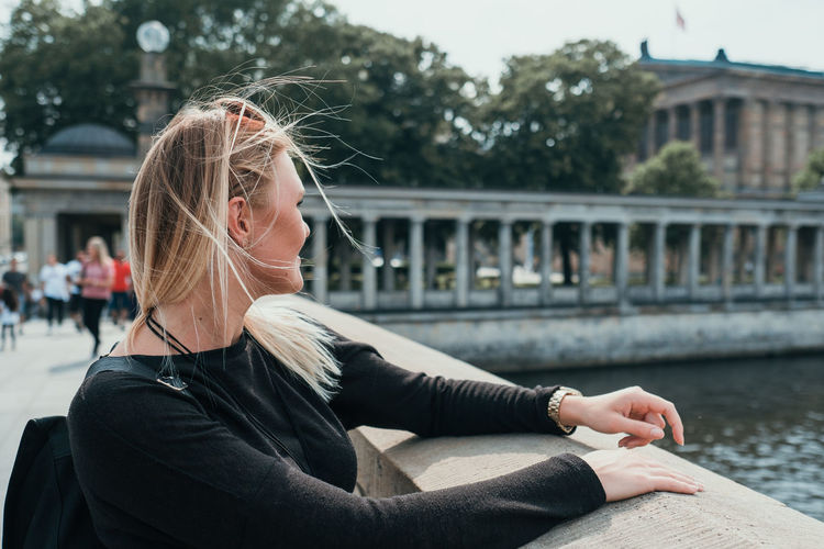 Young woman sitting on bridge over water