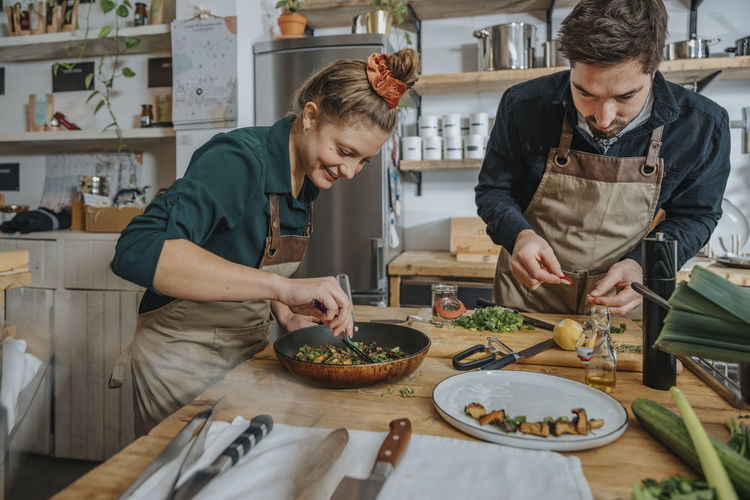 Man and woman standing on table in kitchen