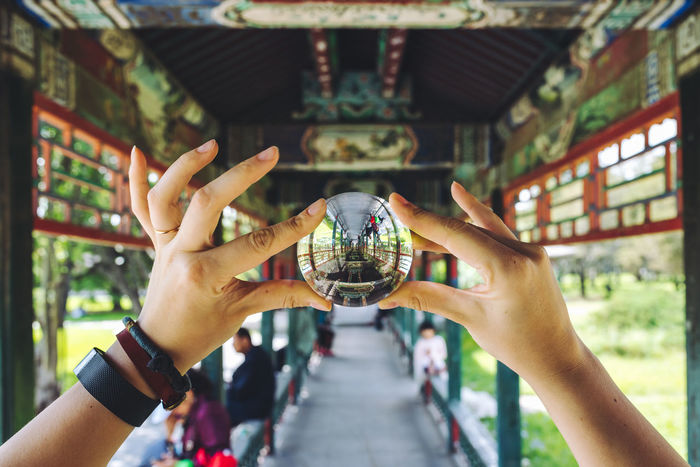 Building through a glass ball. Temple of Heaven Park in Beijing, China Crystal Ball Glass Ball Architecture Built Structure Close-up Day Holding Human Body Part Human Hand Lens Ball Men Outdoors People Photographing Real People Togetherness