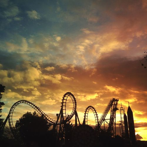 Silhouette Rollercoaster Against Cloudy Sky During Sunset