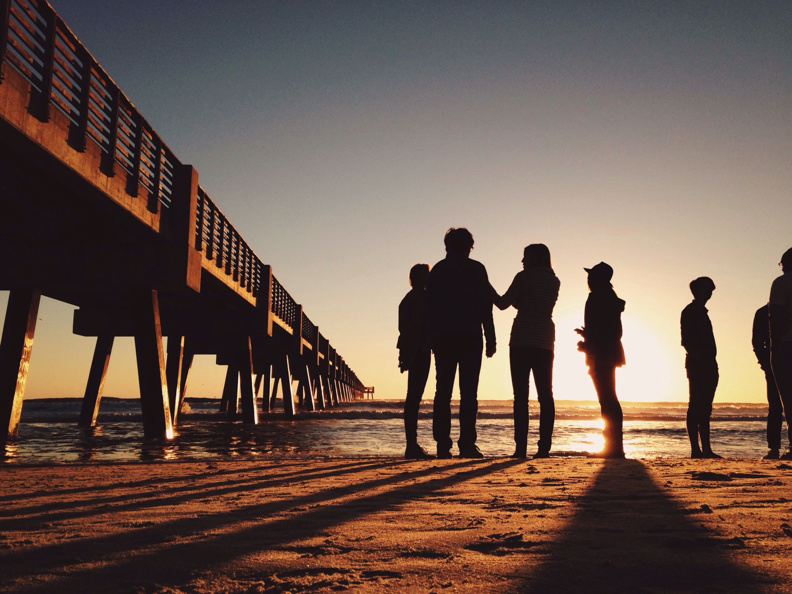 men, silhouette, sunset, clear sky, lifestyles, togetherness, copy space, walking, full length, person, leisure activity, sky, standing, rear view, friendship, sunlight, outdoors, medium group of people