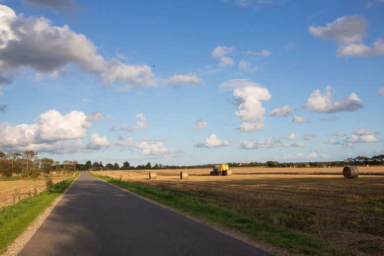 Empty road amidst agricultural field against sky