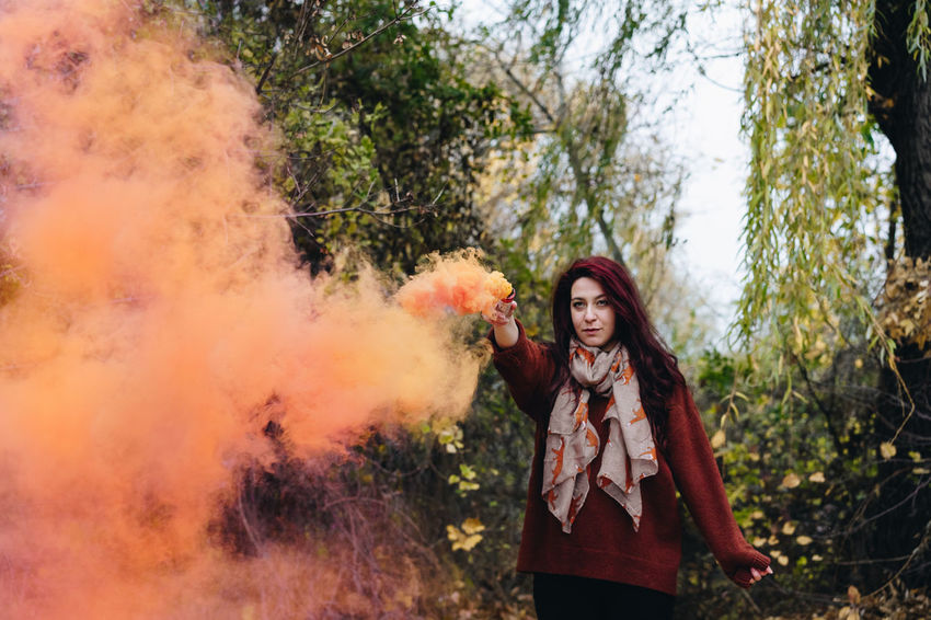 Smoke Smoke - Physical Structure Smoke Bomb Orange Orange Color One Person One Woman Only Tree Holi Young Women Portrait Women Multi Colored Fashion Arts Culture And Entertainment Forest Posing Firework Display Emitting Firework - Man Made Object Smoke Stack Incense Entertainment