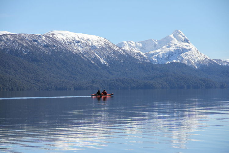 People kayaking on lake against mountains