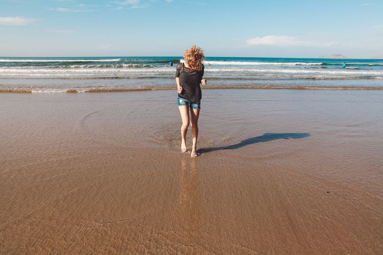 Rear view of young woman walking on beach