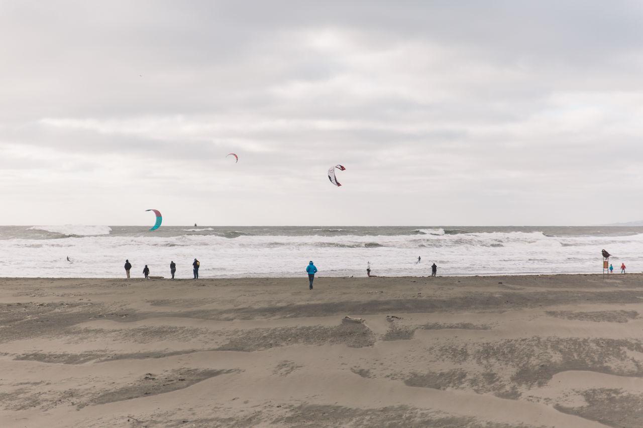 Paragliding At Beach Against Sky