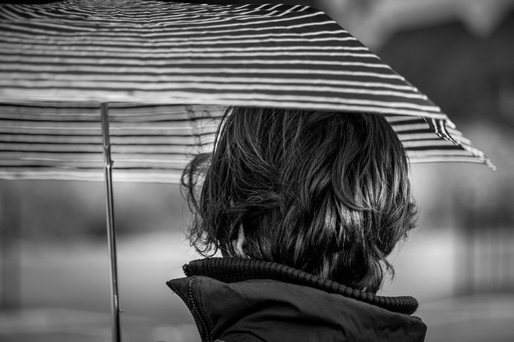Rear view of woman holding umbrella outdoors
